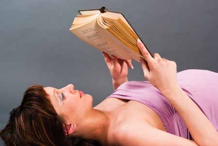 A pregnant woman is lying and reading a book