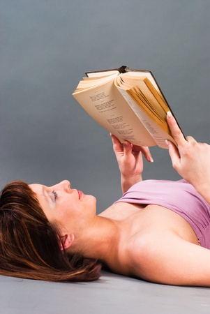 The woman lies on a bed and reading a book Stock Photo
