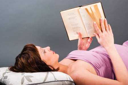 A pregnant woman lies on a bed and reading a book Stock Photo