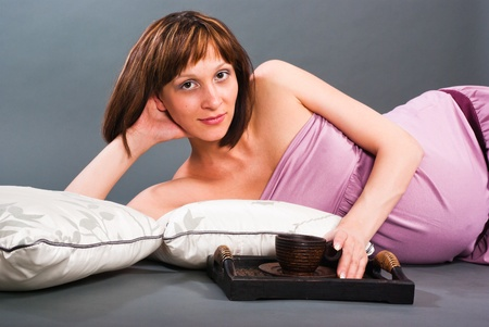 Pregnant woman lying on the cushions with a cup of coffee on a tray