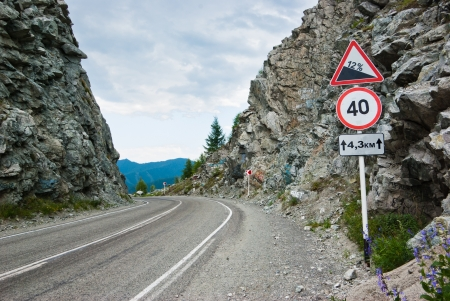 A sign by the road between two rocks, on a mountain pass