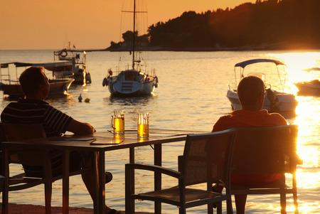 vrienden bier drinken bij zonsondergang Stockfoto