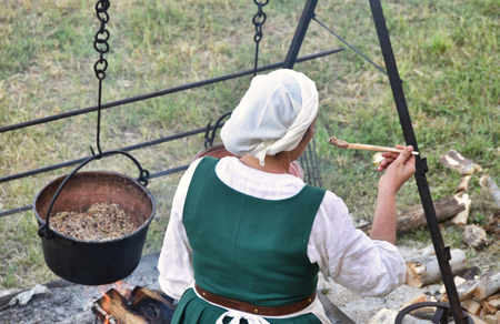 medieval camp kitchen with a chef who tastes food Stock Photo