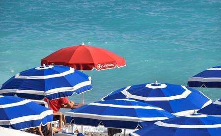 red lifeguard sunshade beach board among blue umbrellas Editorial