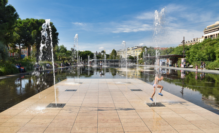 Nice, miroir deau, dancing fountain with jumping child Editorial