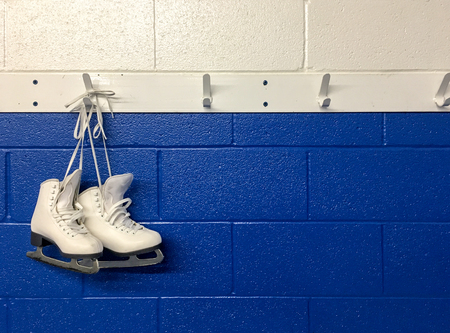 Figure skates hanging on locker room