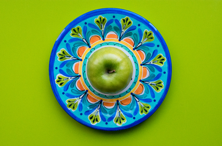 Green apple in Talavera plate with bright green background
