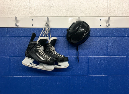 Hockey skates and helmet hanging on locker room with copy space