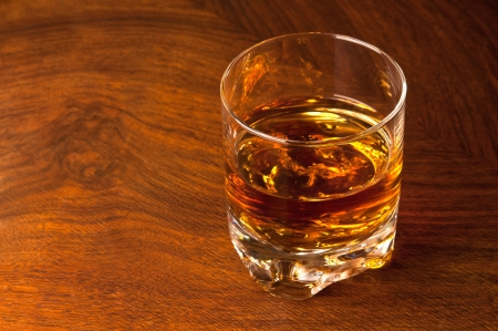 A glass of whiskey on old wooden table