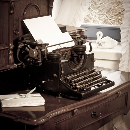 old typewritter with letter paper and envelopes on old desk
