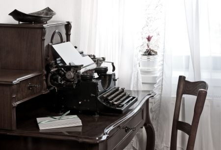 old typewritter with letter paper and envelopes on old desk photo