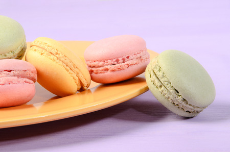 snacking: colorful macarons on a yellow plate