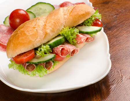 baguette, submarine sandwich, topped with salami, cucumber and tomato