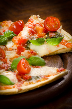 fresh homemade pizza with mozzarella and cherry tomatoes and Basil Standard-Bild