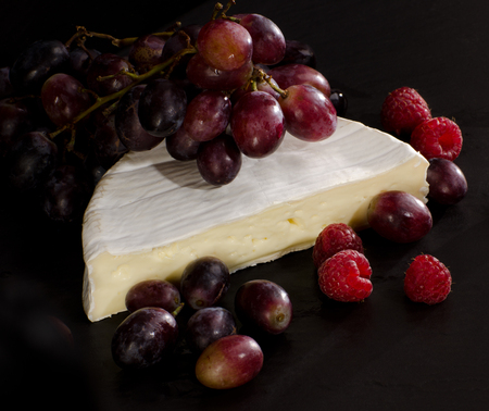 Camembert cheese with grapes and raspberries on black background