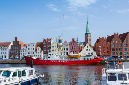 Luebeck, Germany-22 June 2017, view from the Hanseatic harbour to the Jacobi church with the fire-ship Fehmarn Belt in the foreground