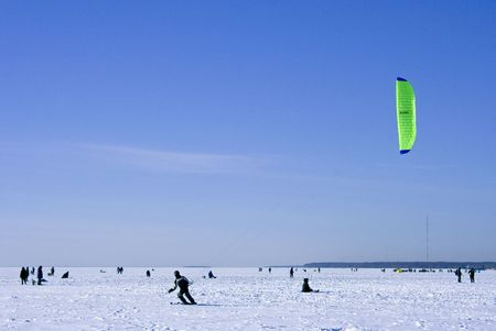 It is a lot of fishers and skyter on an ice of Gulf of Finland in a winter windy sunny day photo
