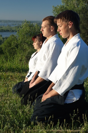 aikido: Three young aikido man meditate before training
