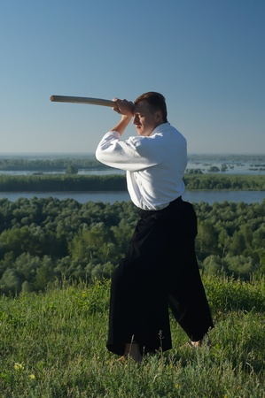 a young man are training in Aikido in the wood photo