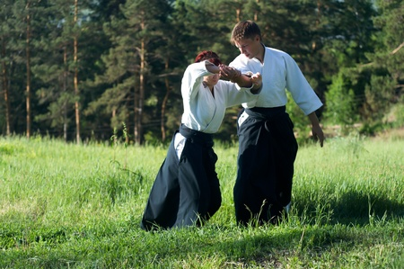 Two young man are training in Aikido in wood photo