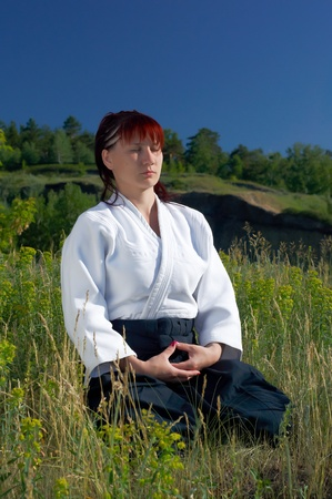 The young girl meditates after employment of an aikido against mountain photo