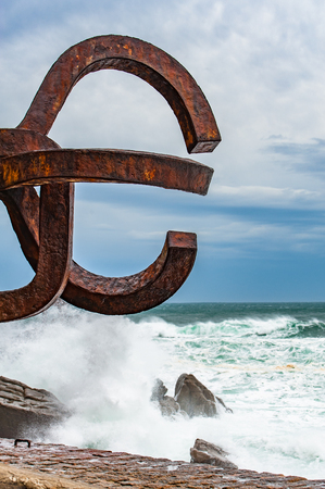 Sculpture The Comb of the winds in San Sebastian , Spain during stormy weather with scenic waves crushing upon stones Editorial