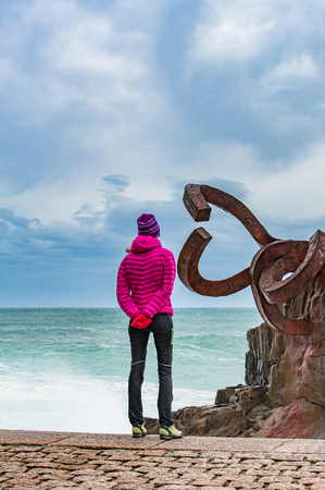 A women observing the sculpture The Comb of the winds in San Sebastian , Spain during stormy weather