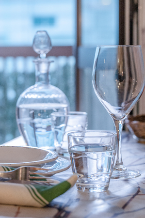 Elegant table set for dinning in a summer with white porcelane dishes, white vintage lace napkin and glassware