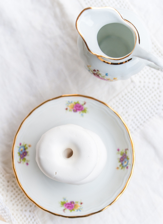 Luxury porcelain tea set on white tablecloth with white glaze bagels on a plate Stock Photo
