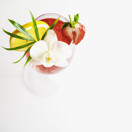Summer cocktail in a martini glass with a tropical flower, slice of lemon, strawberry. Copy space. Stock Photo