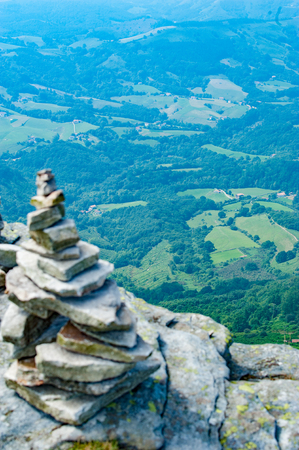Stack of balancing stones on the top of a mountain in French Pyrenees with a view to downhills. Imagens