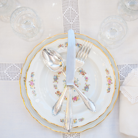 Flatlay with porcelain plates and silver cutlery with lace napkins on an antique tablecloth. Stock Photo