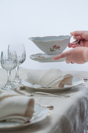 Women hands placing a saucer on a table served with porcelain dinnerware. Selective focus.