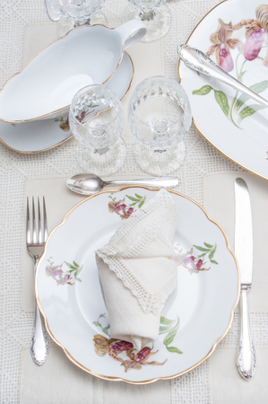 Fine dinning: floral pattern white china dinner set arranged on a table with vintage tablecloth and napikins, crystal glassware. Selective focus.