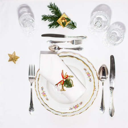 Christmas dinner set: porcelain plates, silver cutery and white napking lying via diagonal line with christmas decoration. Flatlay. Copy space.