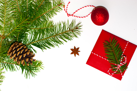 Christmas concept: red envelope decorated with a pine branch, christmas candy cane with christmas toys, anise star and pine cone on white background. Copy space. Flatlay.