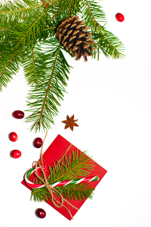Christmas concept: red envelope decorated with a pine branch, red berries, christmas candy cane with christmas toys, anise star and pine cone on white background. Copy space. Flatlay.