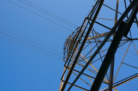 against the current: An electricity transmission tower rises overhead, casting its metal frame against the blue sky, as power lines extend in both directions, carrying their electrical current.