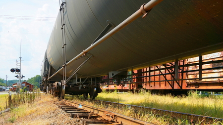 freight train: A black oil tanker freight train sits on railroad tracks at a rural train station.