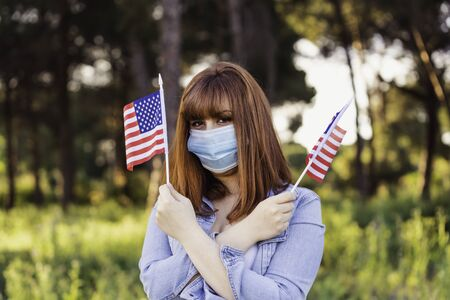 girl in protective medical mask with flags of United States of America in hands in nature. July 4 United States Independence Day. Health protection, safety and pandemic concept