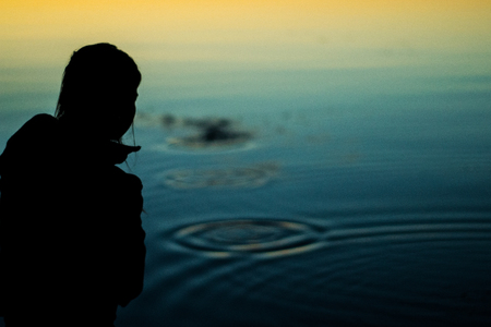 A silhouette of a woman skipping a rock on a sunset lake. Banco de Imagens