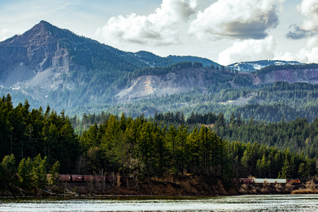 A shot over the river capturing a train passing by the mountians. Stock Photo