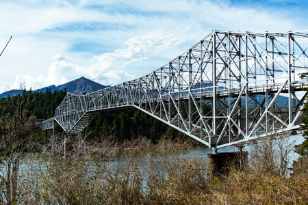 A shot of a truss bridge extending over the river. The mountains in the background complement this photo well.
