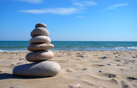 close up view of six zen stones in a beach with room for text Stock Photo