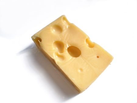Close up view of a piece of Emmental Cheese on a white background