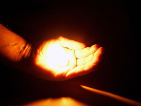 hand holding a flame         photo