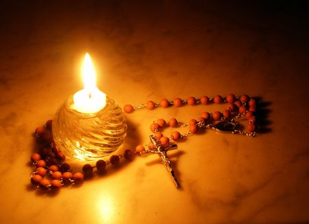 Rosary and candle     Stock Photo