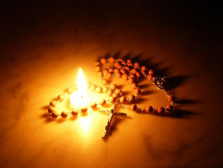 burning love: Candle and Rosary Stock Photo