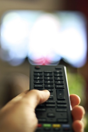sports programme: Hand holding a TV remote control device Stock Photo