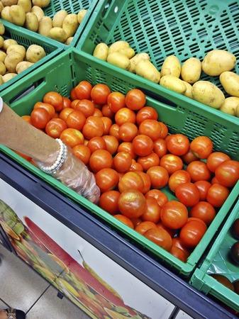expositor: mano de mujer recogiendo tomates en un supermercado